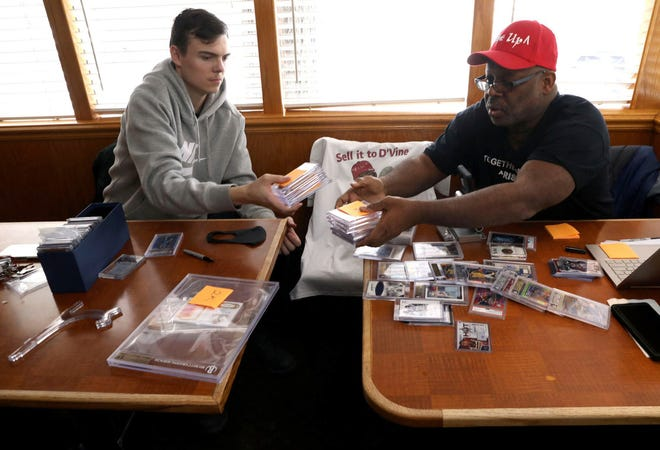 Sports card collectors Brandon Sommers, left, and Anthony Dovine select cards, haggle over prices and joke around over sports cards worth thousands at a corner table inside the Red Apple Pancake House in Carol Stream, Ill. on Feb. 11, 2021.