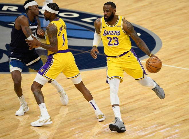 The Los Angeles Lakers' Kentavious Caldwell-Pope (1) sets a pick for the Minnesota Timberwolves' Jarred Vanderbilt (8) as teammate LeBron James dribbles past during the first quarter at Target Center in Minneapolis on Tuesday, Feb. 16, 2021. The Lakers won, 112-104.
