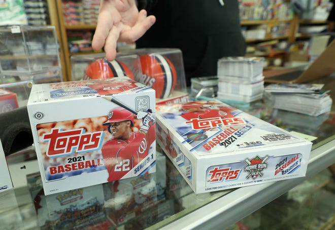 Jim and Steve's Sportscards owner Steve Wilson describes the contents of the 2021 Topps first series baseball cards released on Feb. 10, in Waukegan. Trading cards have seen an increase in popularity during the COVID-19 pandemic.