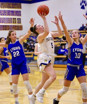 Josie McLean drives to the basket past Lyons' Kayleigh Arriola (22) and Caitlyn Belote (10) during their game in Nickerson Tuesday night. Nickerson defeated Lyons 64-42.