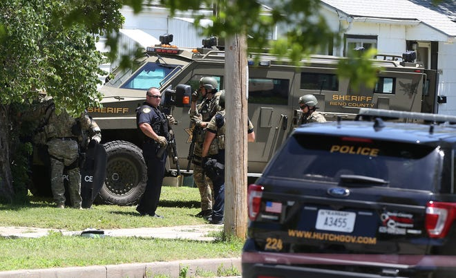 Law enforcement officers from the Hutchinson Police Department and the Reno County Sheriff's Office work together during a standoff at a home in Hutchinson on June 20, 2019.