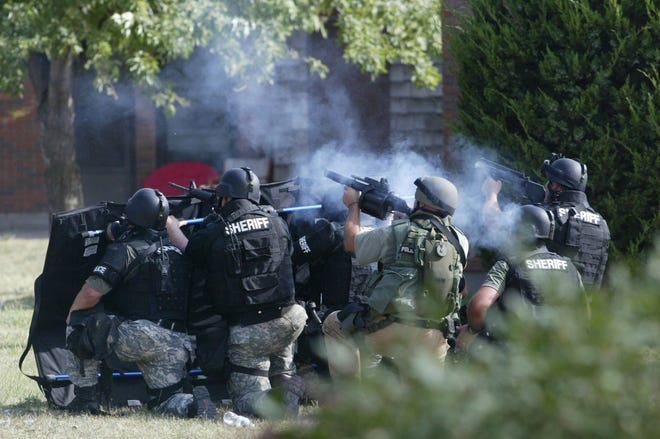 Members of the joint Hutchinson Police, Reno County Sheriff's Emergency Response Team fire teargas into an apartment at The Clusters in this 2013 file photo. The joint ERT has been disbanded after some 15 years, with each agency now having its own team, though they have agreed to respond to each other's calls as needed.