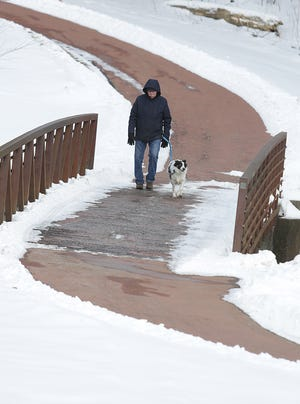 Area resident Tim Paul walks with his dog, Mikey, on Wednesday afternoon along the Campbell Walking Trail at Reservoir Park. The Massillon Recreation Board has agreed to fund a $49,000 resurfacing effort for the path.