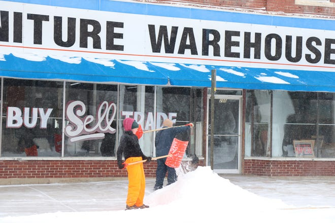 Even as temperatures continued to dip below zero, downtown business owners braved the cold to clear sidewalks when fresh snowfall occurred Tuesday morning. For more winter photos by Michele Clark, visit thekansan.com.