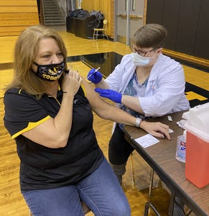 Ellen McClure, director of human resources for the Cuyahoga Falls City School District, receives the first dose of the COVID-19 vaccine at Cuyahoga Falls High School Saturday, Feb. 13. About 470 district employees were vaccinated by Discount Drug Mart pharmacists.