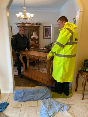 Detective Ethan Crockett and Patrol Supervisor Jason Horton removing furniture from the water soaked area of the home.