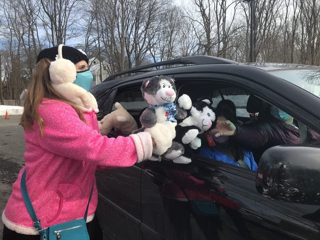 Heather Johnston, co-founder of Marlborough-based Kits for Kids, hands out stuffed animals to a family inside a car during the organization's free toy drive, Feb. 13, 2021, in Framingham.