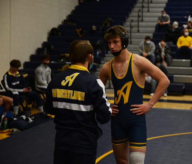 Airport assistant coach Logan Griffin talks with Jack Mills earlier this season. Mills is off to a 14-0 start to his high school wrestling career.