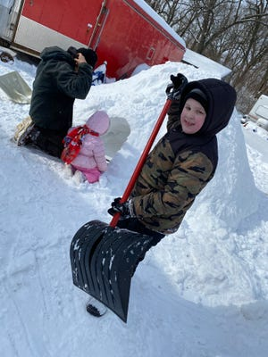 Terry Pierce Jr., 7, and Elliana Pierce, 2, help their dad, Terry Pierce, build an igloo in their driveway on Blue Bush Rd. after 10 inches of snow fell this week.