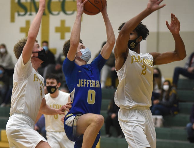 Nathaniel Frames of Jefferson goes to the hoop with pressure from Jaden Turner and Cyrus Marks of SMCC Tuesday night. [MONROE NEWS PHOTO BY TOM HAWLEY]