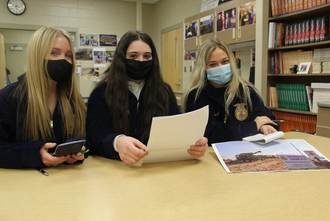 Nevada FFA chapter officers review grain inventory and prices, left to right, Chloe Henry, Bianca Sponsellerand Ellie Moser. Not pictured Kevin Cooper, Nevada FFA agriculture education instructor and FFA advisor.