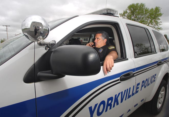 Yorkville police officer Patrick Collea takes a call while monitoring motorists traveling along Oriskany Boulevard in this OD file photo.