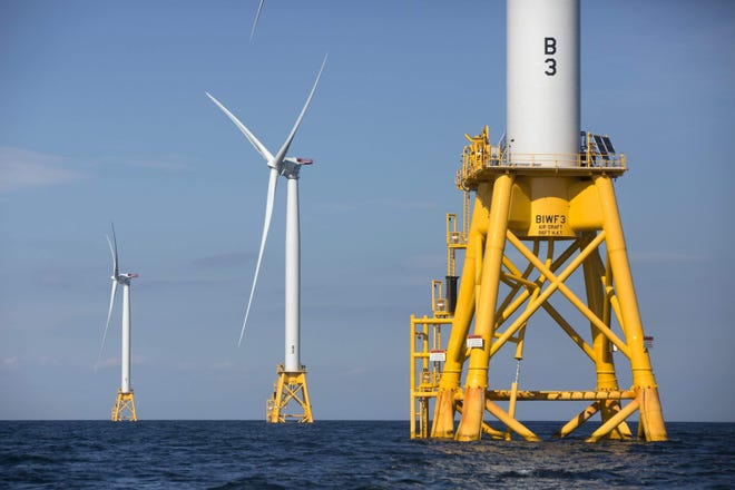 Three wind turbines from the Deepwater Wind project stand in the Atlantic Ocean off Block Island, Rhode Island.
