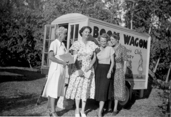 Women standing next to Coco Plum Woman's Club public library book wagon in South Miami.