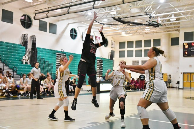 Palm Beach Lakes senior captain Zaida Gonzalez rises above Jupiter defenders to attempt a jumper in the second period of the Rams' regional semifinals victory against Jupiter. Gonzalez added 10 points as the primary ball-distributor in the Lakes attack.