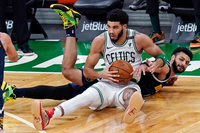 Celtics forward Jayson Tatum, center, gains control of the ball from Denver's Jamal Murray on Tuesday night. Tatum is still dealing with the after-effects of COVID-19.