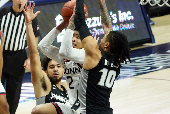 Connecticut guard James Bouknight squeezes between Providence guards Jared Bynum, left, and Alyn Breed (10) during the first half of Tuesday night's Big East game.