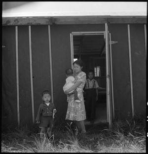 A Japanese-American family wait at the door of the room in the barracks to which they have been assigned on their first day at the Japanese War Relocation Center at the San Joaquin County Fairgrounds in Stockton on May 19, 1942. The father was at the baggage depot, where their bedding and clothing were unloaded and inspected for contraband.