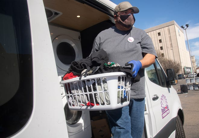Volunteer Ron Amador carries a basket of clean clothes from the Loads of Hope mobile laundromat at St. John the Evangelist Episcopal Church in downtown Stockton.