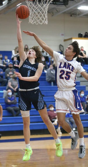 Will Aljancic (1) of Louisville flies to the basket while being guarded by Landon Woods (25) of Lake during their game at Lake on Tuesday, Feb. 16, 2021.
