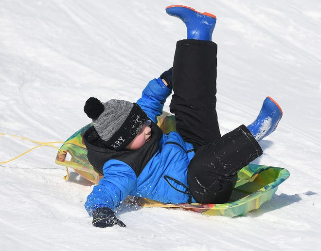 T.C. Knapp kindergartener Brody McMullan tries to hang on while sledding down a hill behind the school during his physical education class on Wednesday.