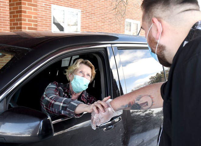 Judy Carneal of North Canton greets Rev. Jake Heskett during a drive thru Ash Wednesday event at Faith United Methodist Church in North Canton.