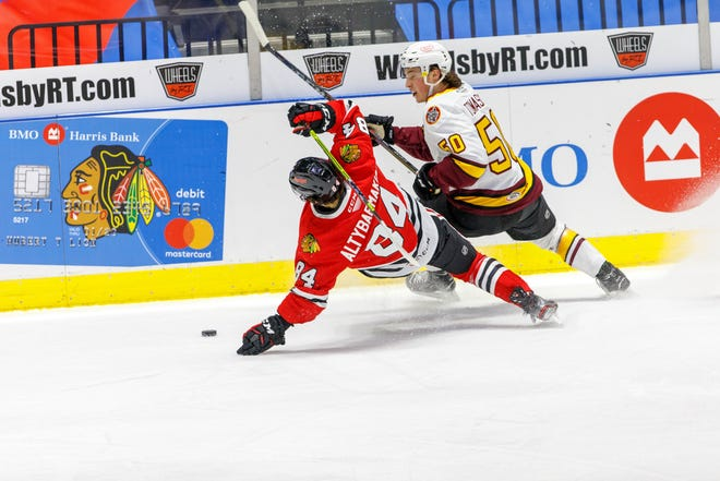 IceHogs winger Andrei Altybarmakyan goes to the ice while battling Chicago's Philip Tomasino for the puck in Rockford on Tuesday, Feb. 16, 2021.