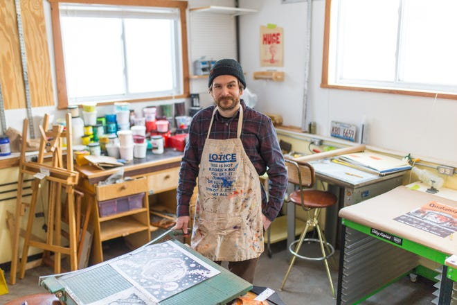 Joe Tallman is a finalist in the Pabst Blue Ribbon beer can design competition. He poses for a portrait with early drafts of his design at his home studio on Wednesday, Feb. 17, 2021, in Rockford.