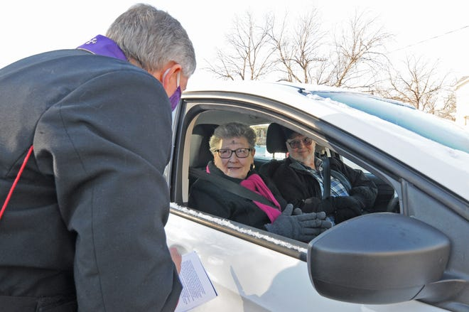 """The Very Rev. David Hodges visits with Denise and Michael DuBois after giving them ashes during the Ash Wednesday drive-thru in the Christ Cathedral parking lot in Salina.  """"We are not going to church out of precaution of COVID-19 we have been watching the church services online,"""" Denise DuBois said."""