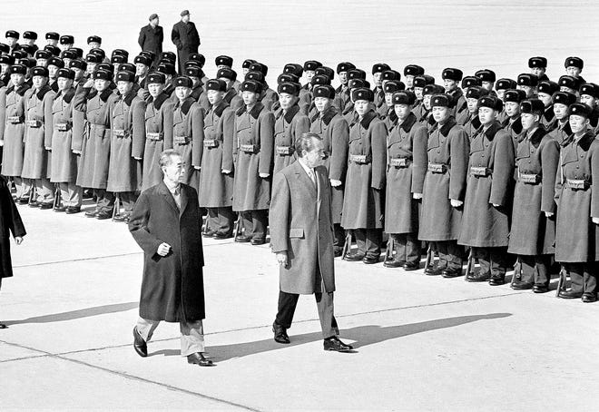 President Richard Nixon is greeted by Chinese Premier Chou and troops a line of troops at the Peking airport Feb. 21, 1972.