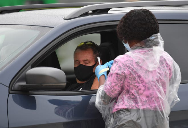 A driver rolls up his sleeve to get a vaccination on Feb. 17, the first day of a three-day coronavirus vaccine clinic in Lakewood Ranch. One thousand vaccines were offered each day to residents in the 34202 and 34211 ZIP codes who had registered for Manatee County's vaccine pool.