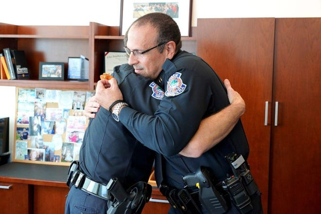 Sarasota Police Chief Jim Rieser presents newly appointed Deputy Chief Rex Troche with his badge Tuesday.