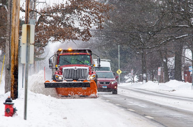 A Springfield Public Works snow plow tries to clear a snow covered lane along West Lawrence Avenue in Springfield, Ill., Wednesday, February 17, 2021. A snow emergency in Springfield was lifted Thursday.
