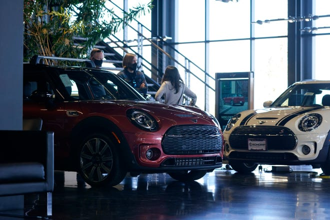 In this October 29, 2020, photo, a salesperson interacts with shoppers at a Mini dealership in Highlands Ranch, Colorado. One option to get out of a leased vehicle you no longer want is to trade it in for a different vehicle at a dealership. (AP photo/David Zalubowski)