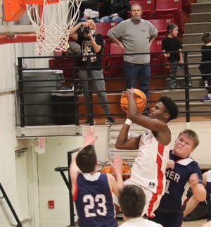 Earlsboro's Dante Hall (5) goes in for a shot between Asher's Cameron Grissom (23) and Tray O'Dell (21) Saturday in a Class B district final Saturday in Earlsboro. The host Wildcats won the game, 38-35.