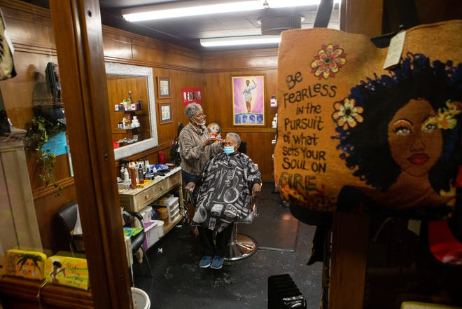 Lenora Williams, owner and operator of Heavenly Creations Salon and Boutique,117 S.W. 6th St., finishes cutting the hair of Lenora Netherland on Wednesday afternoon. Williams had pulled funds from a retirement savings to keep the business afloat.