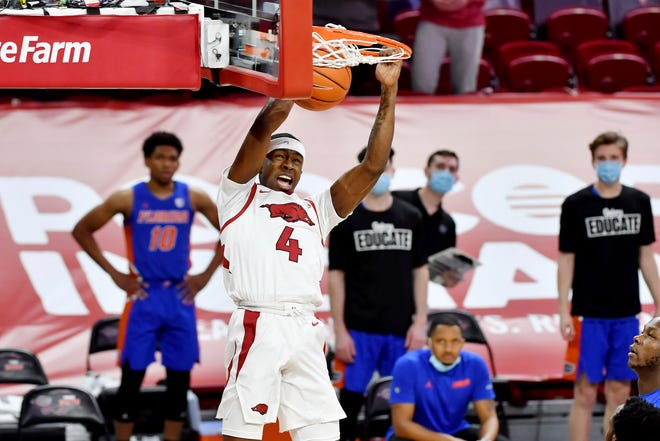 Arkansas guard Davonte Davis (4) dunks the ball against Florida during the first half of an NCAA college basketball game in Fayetteville, Ark. Tuesday, Feb. 16, 2021. (AP Photo/Michael Woods)