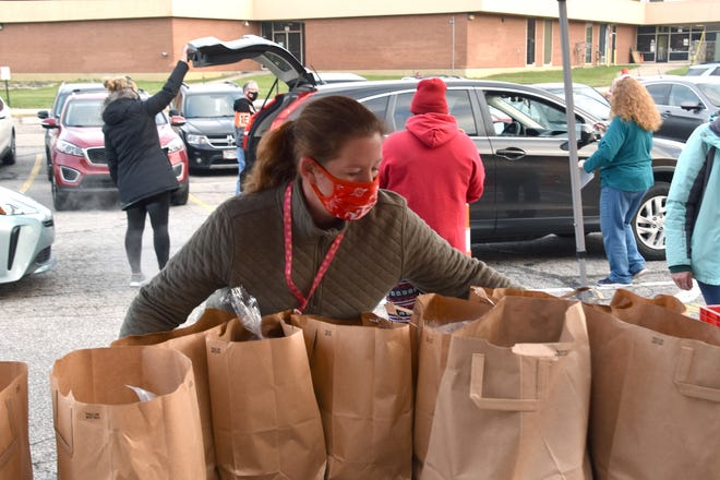 Jennifer Gillespie, a food-services worker at Pointview Elementary School, organizes bags filled with food for families at Westerville City Schools' drive-thru meal pickup Dec. 5.