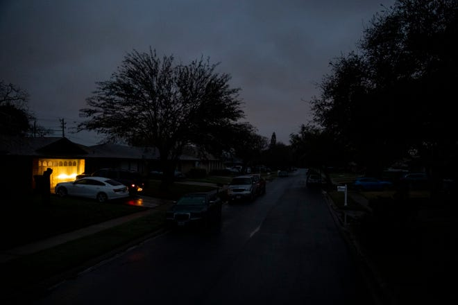 A car idles in a driveway on Jordan Drive, a street with no power early Wednesday morning Wednesday, Feb. 17, 2021. Texas was hit earlier in the week by frigid temperatures that left millions of customers without power.