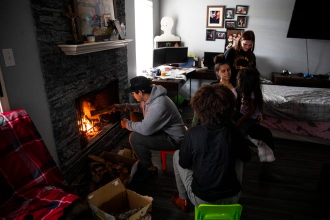 Emilio Venegas puts wood on the fire as his kids, siblings and neighbors keep warm in his living room having been without power for over 48 hours in freezing temperatures in Corpus Christi, Texas on Wednesday, Feb. 17, 2021.