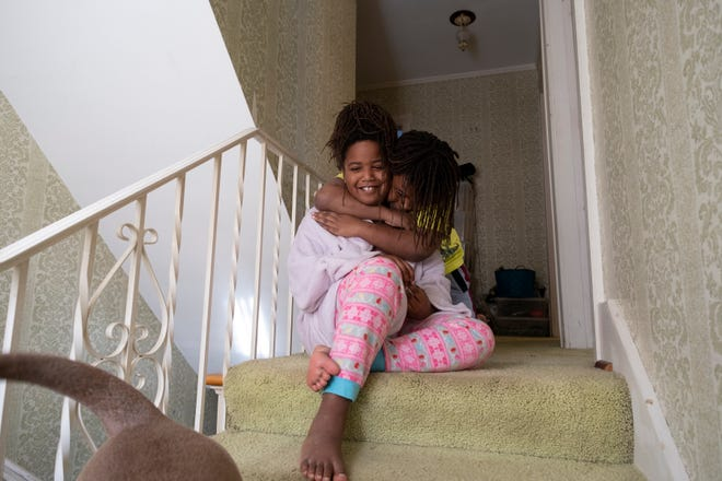 Photographer Yvette Rock focused on motherhood during her Facing Change: Documenting Detroit fellowship. In this image, one of her subjects' children, Ife (left) and Ade (right) hug on top of the stairs while watching their dog.