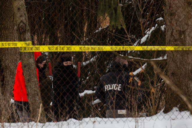 """Portage police investigate the backyard of a home in Portage, Mich. on Tuesday, Feb. 9, 2021. Police checking on a Kalamazoo-area man who didn't report to work online put yellow tape around the property. Officers also brought shovels to the backyard. Gary and Laura Johnson, both in their mid-60s, were not at their Portage home, but officers found """"signs of violence."""" Public Safety Director Nick Armold says there's no """"rational explanation"""" for their disappearance."""