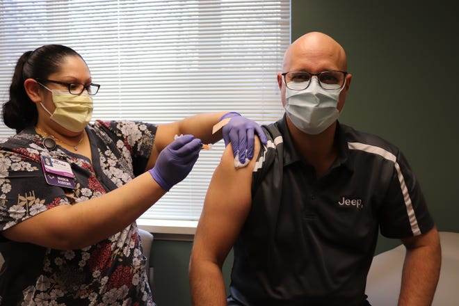 Mark Kreusel, Belvidere Assembly Plant Manager, (right) gets the COVID-19 vaccine as part of a Boone County, Illinois pilot program started on Feb. 2, 2021.