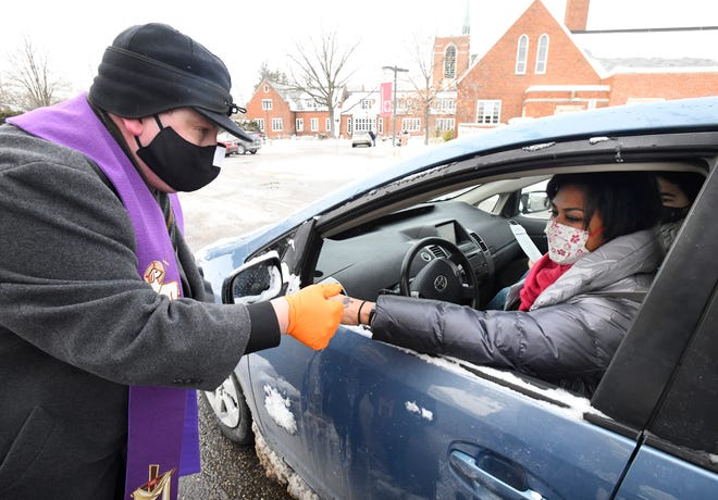 """Birmingham First United Methodist Church  Senior Pastor Elbert Dulworth shares ashes with Andrea Whan on her hand during a Stations of Lent drive-thru event held by the church on Wednesday, Feb. 17, 2021, Ash Wednesday. """"We didn't want to put our hands in people's faces,"""" Dulworth said. """"We have an opportunity for them to take their own ashes if they want to do it themselves as well.  We are just trying to do what is most comfortable for each person."""""""