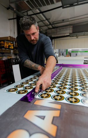 Christopher Saner, a graphic specialist at Brand 1 Ink in Cape Coral, cuts custom stickers after printing.