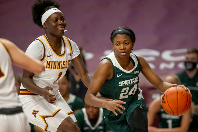 Michigan State guard Nia Clouden brings the ball up court past Minnesota guard Alexia Smith (1) during an NCAA basketball game on Wednesday, Dec. 9, 2020, in Minneapolis. Michigan State won 81-68. (AP Photo/Bruce Kluckhohn)