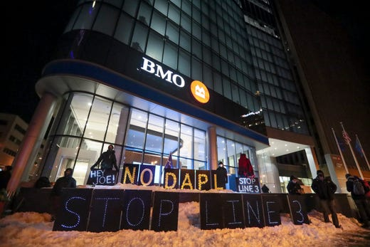 Two protests occur Tuesday, Feb. 16, 2021, outside of BMO Harris Bank and City Hall before President Biden speaks at the Pabst Theater in Milwaukee.