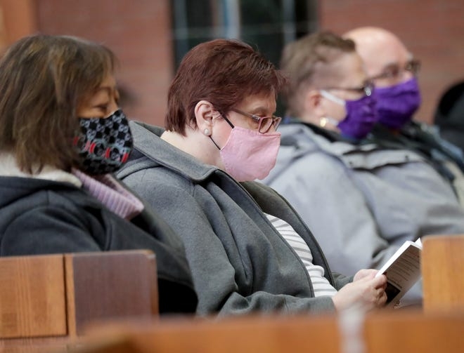 Parishioners attend mass with masks during an Ash Wednesday service at Blessed Sacrament Congregation on South 41st Street, Wednesday, Feb. 17, 2021 in Milwaukee. Due to Covid-19, the ashes were sprinkled on the top of parishioners heads rather than the traditional method of being signed on the forehead with an ash cross.   - Photo by Mike De Sisti / Milwaukee Journal Sentinel