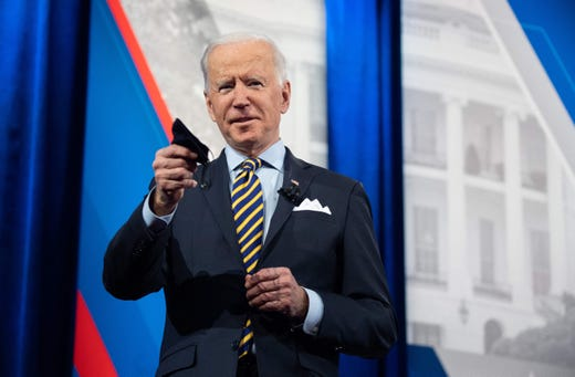 President Joe Biden participates in a CNN town hall at the Pabst Theater in Milwaukee, Wisconsin, on Feb. 16, 2021. Biden is holding a face mask.