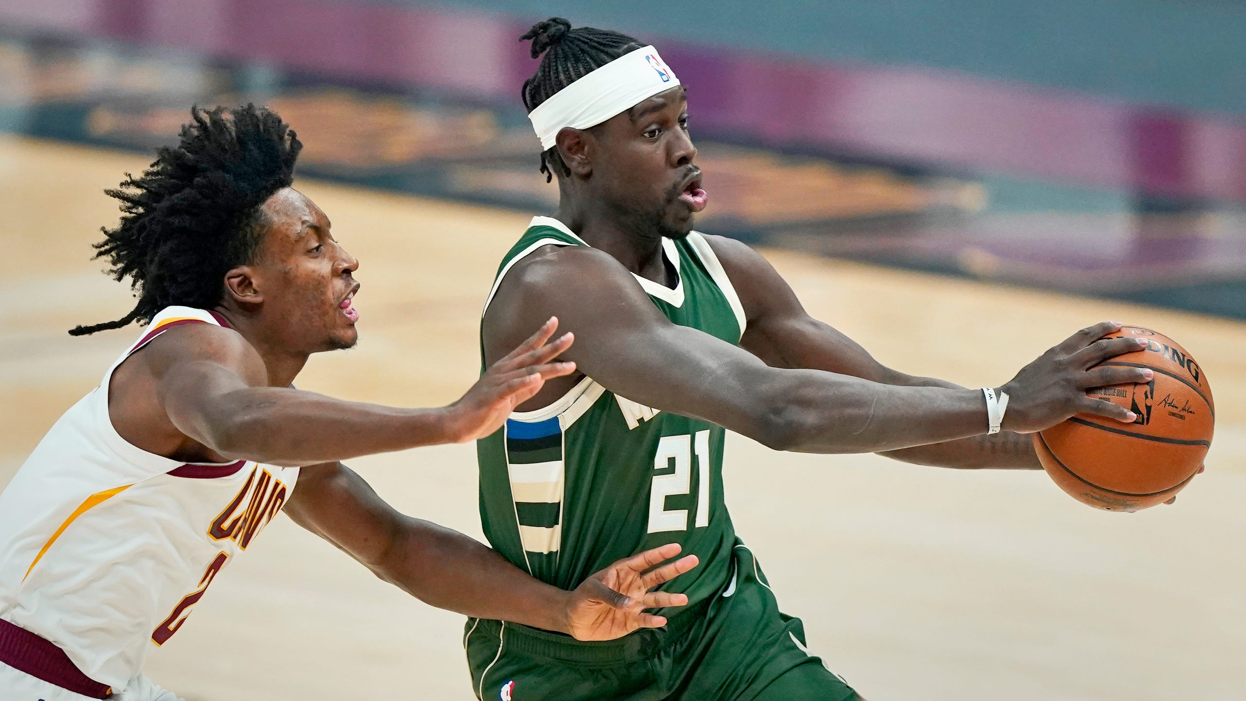 Milwaukee Bucks' Jrue Holiday (21) drives against Cleveland Cavaliers' Collin Sexton (2) in the first half of an NBA basketball game, Saturday, Feb. 6, 2021, in Cleveland. (AP Photo/Tony Dejak) ORG XMIT: OHTD106